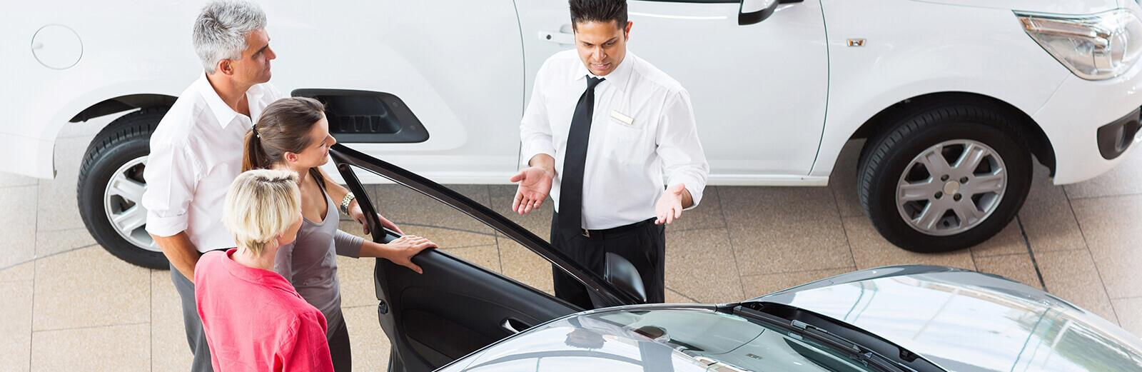salesman with customers showing car